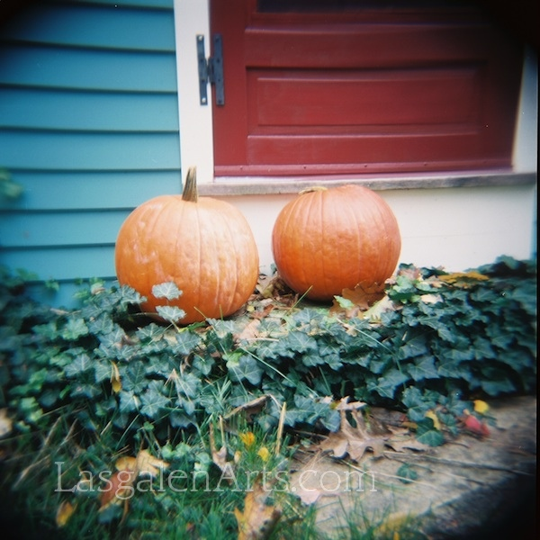 Two pumpkins sits on a doorstep.