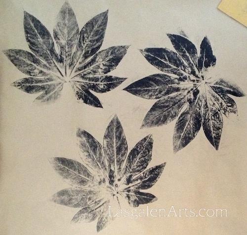 Three black leaf prints on brown paper.