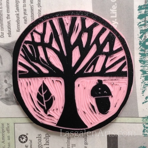 Round pink stamp designed with tree, leaf and acorn.
