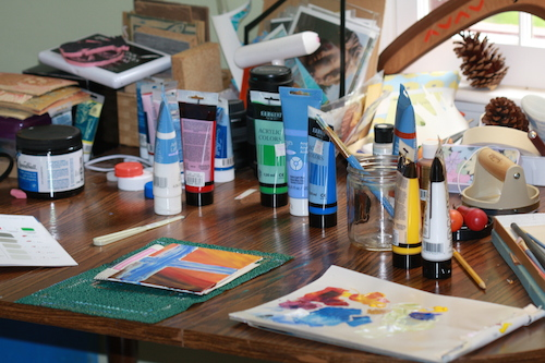 Artist's table with paints, printmaking supplies and painting visible.