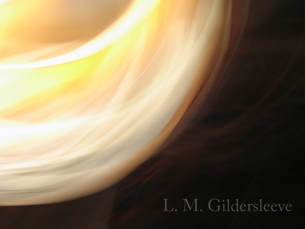 An abstract photograph of golden light swirling against a black background.