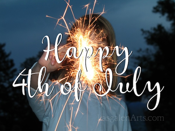 A girl holding a sparkler with a 4th of July message.