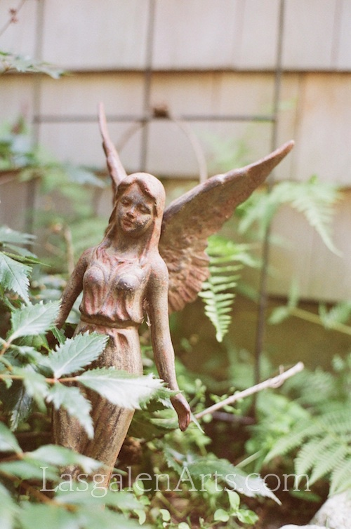 Photograph of a garden angel made of iron.
